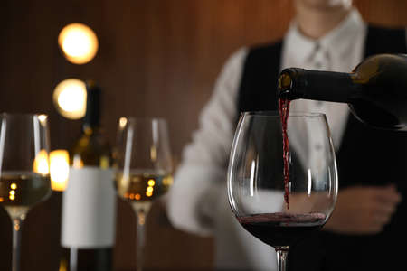 Waitress pouring wine into glass in restaurant, closeup Stock fotó