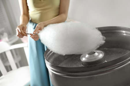 Woman making cotton candy using modern machine indoors, closeup Stock Photo