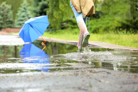 Woman in rubber boots running after umbrella on street, closeup. Rainy weather