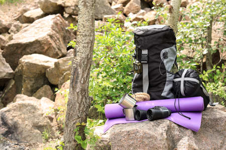 Backpack and camping equipment on stone in forest. Space for text Фото со стока