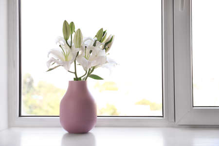 Vase of beautiful lilies on windowsill indoors, space for text Stockfoto