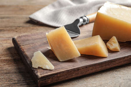 Board with cut Parmesan cheese on wooden table Stock Photo
