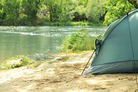 Modern camping tent on riverbank in wilderness. Space for text Фото со стока