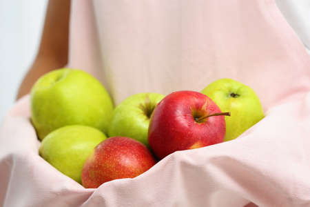 Woman holding pile of apples with hem of apron, closeup Stock Photo - 128780202