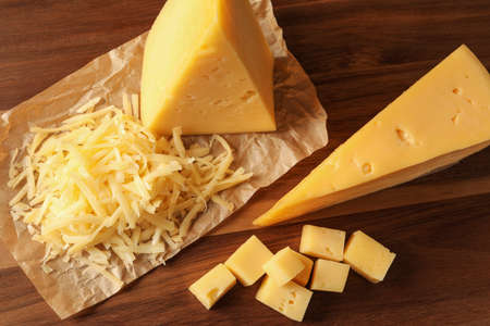 Grated and cut delicious cheese on wooden background, top view Stock Photo