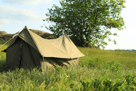 Camping tent in green field on sunny day. Space for text Фото со стока