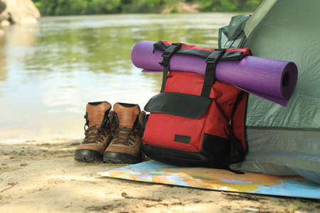 Modern camping tent and equipment on riverbank. Space for text Фото со стока