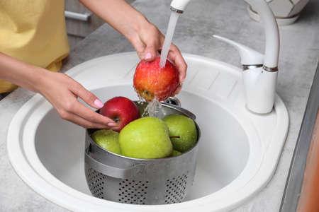 Woman washing fresh apples in kitchen sink, closeup Stock Photo - 128780219