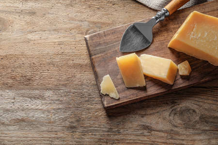 Board with cut Parmesan cheese on wooden background, top view. Space for text Stock Photo - 128780245