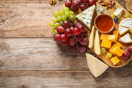 Flat lay composition with board of delicious cheese and snacks on wooden background. Space for text