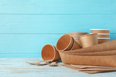 New paper dishware on table against light blue wooden background, space for text. Eco life