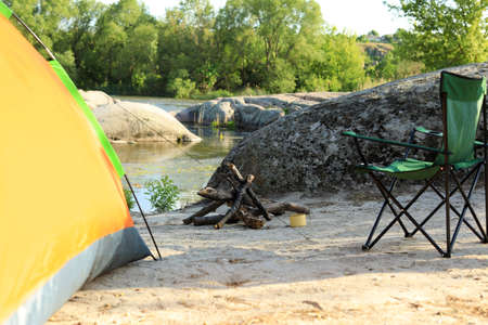 Modern camping tent with chair and firewood on riverbank