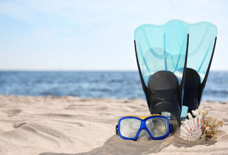 Diving mask, flippers and seashells on sand near sea, space for text. Beach objects