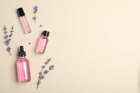 Bottles of essential oil and lavender flowers on beige background, flat lay. Space for text