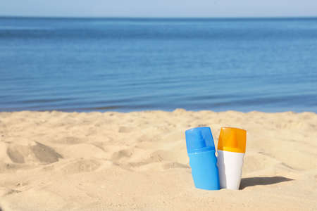 Bottles of sunblock in beach sand near sea. Space for text