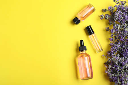 Bottles of essential oil and lavender flowers on yellow background, flat lay. Space for text