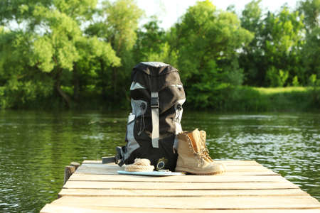 Backpack and camping equipment on wooden pier near river