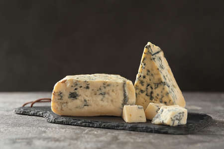 Slate board with delicious blue cheese on stone surface