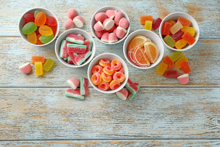 Flat lay composition with bowls of different jelly candies on wooden background. Space for text Stockfoto