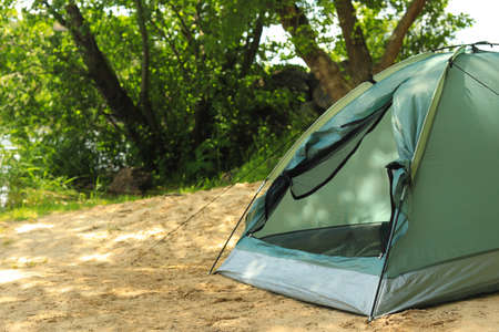 Modern camping tent near trees in wilderness