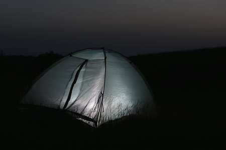 Modern tent lit from inside in wilderness at night, space for text. Overnight camping Фото со стока