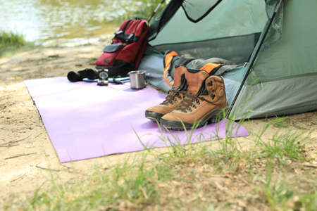 Boots and camping equipment near tent on riverbank. Space for text