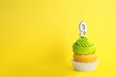Birthday cupcake with number nine candle on yellow background, space for text Stock fotó
