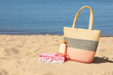 Stylish beach accessories on sand near sea. Space for text