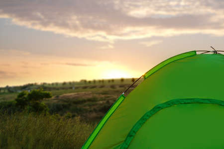 Modern camping tent in wilderness at sunset. Space for text