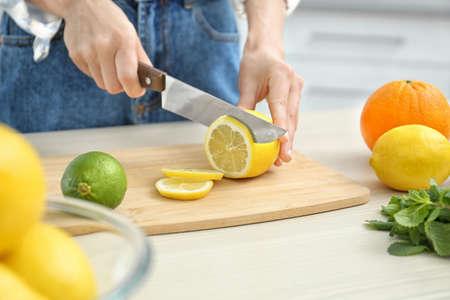 Woman cutting fruit for making natural detox lemonade at table in kitchen, closeup Stock Photo