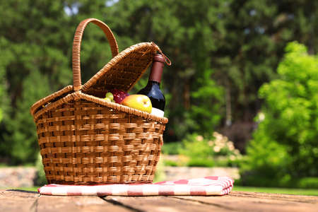 Picnic basket with fruits, bottle of wine and checkered blanket on wooden table in garden Zdjęcie Seryjne