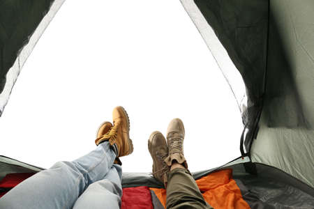 Closeup of couple in camping tent on white background, view from inside