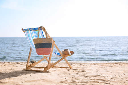 Lounger, hat and bag on sand near sea, space for text. Beach objects Stockfoto