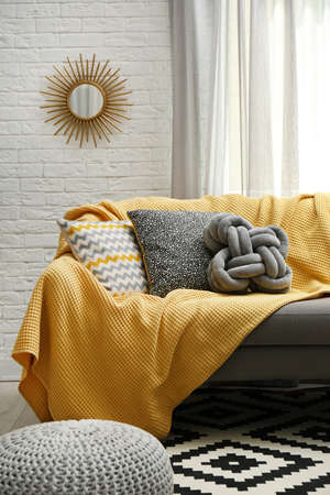 Soft pillows and yellow plaid on sofa in living room Stock fotó