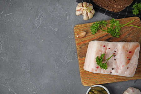 Board with pork fatback, garlic, parsley, bread and bowl of pickles on grey stone background, flat lay. Space for text