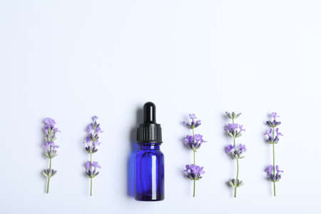 Bottle of essential oil and lavender flowers on white background, flat lay