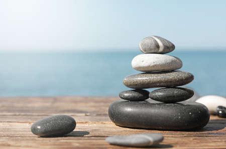 Stack of stones on wooden pier near sea seascape, space for text. Zen concept Banco de Imagens