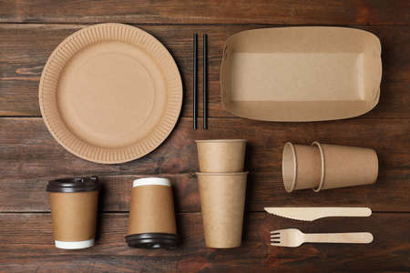Flat lay composition with new paper dishware on wooden background. Eco life