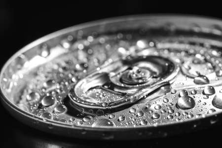 Aluminum can of beverage covered with water drops on black background, closeup