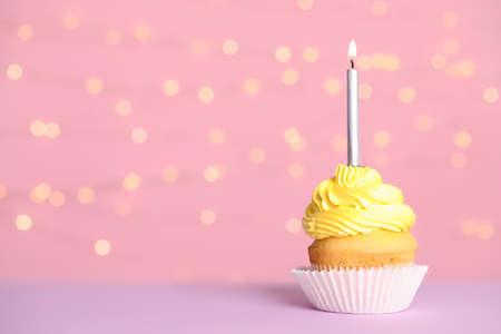 Cupcake de cumpleaños con velas en la mesa contra luces festivas, espacio para texto