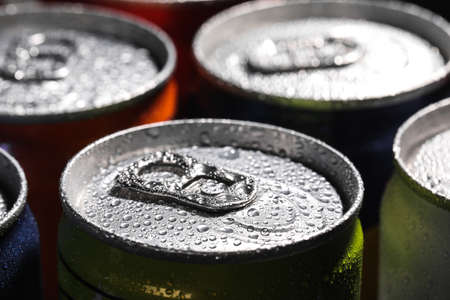 Aluminum cans of beverage covered with water drops as background, closeup