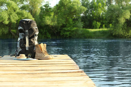 Backpack and camping equipment on wooden pier near river. Space for text Фото со стока