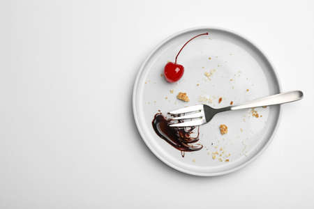 Dirty plate with food leftovers, fork and canned cherry on white background, top view