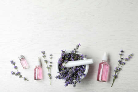 Bottles of essential oil, mortar and pestle with lavender flowers on white wooden background, flat lay. Space for text