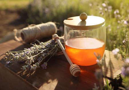 Jar of honey on wooden table in lavender field Zdjęcie Seryjne