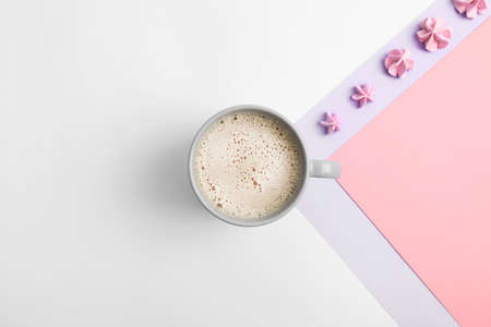 Cup of coffee and meringues on color background, top view. Space for text