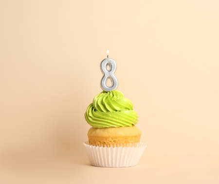 Birthday cupcake with number eight candle on beige background Stock fotó