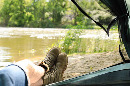 Young man resting in camping tent on riverbank, view from inside