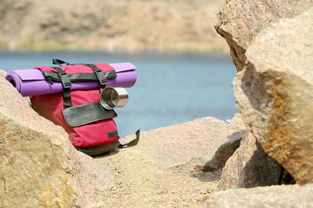 Camping backpack with mat and mug on stones near river. Space for text