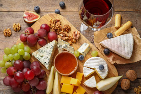 Flat lay composition with board of delicious cheese and snacks on wooden background Stock Photo